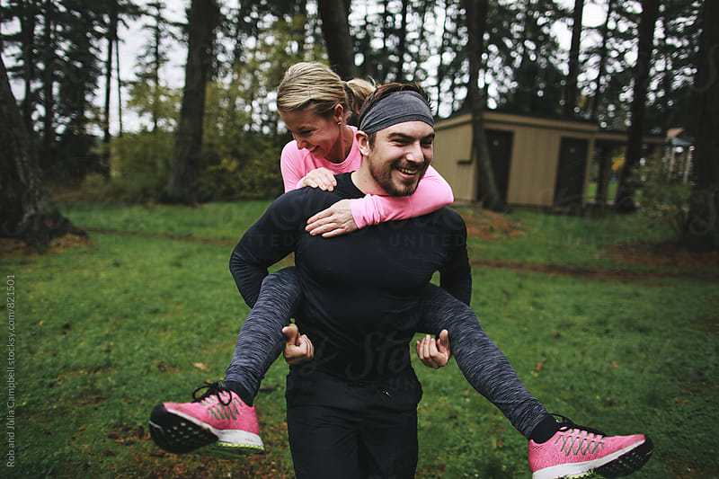 Caucasian man and woman doing piggy-back rides in workout clothes outside by Rob and Julia Campbell for Stocksy United