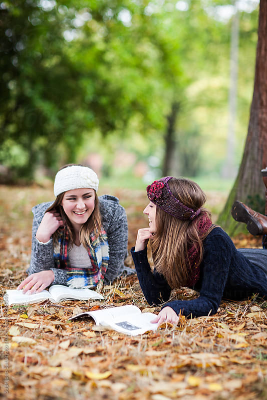 Two female college students studying outdoor lying down on the grass by Suprijono Suharjoto for Stocksy United