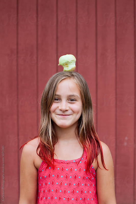 Girl balances half eaten apple on her head by Carleton Photography for Stocksy United