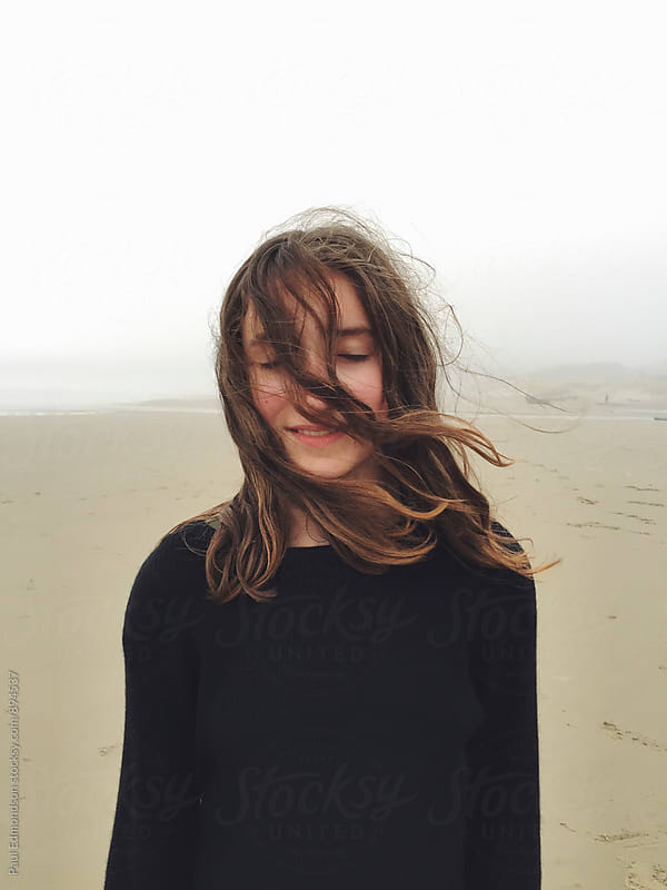 Portrait of twelve year old girl on beach, eyes closed with hair covering face by Paul Edmondson for Stocksy United