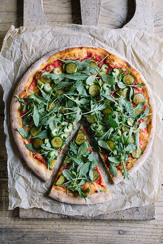 Sliced italian pizza with courgette and arugula on wooden table by Alberto Bogo for Stocksy United