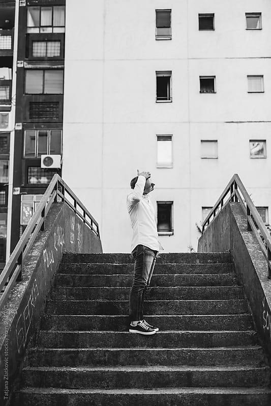 Young man in urban environment by Tatjana Zlatkovic for Stocksy United