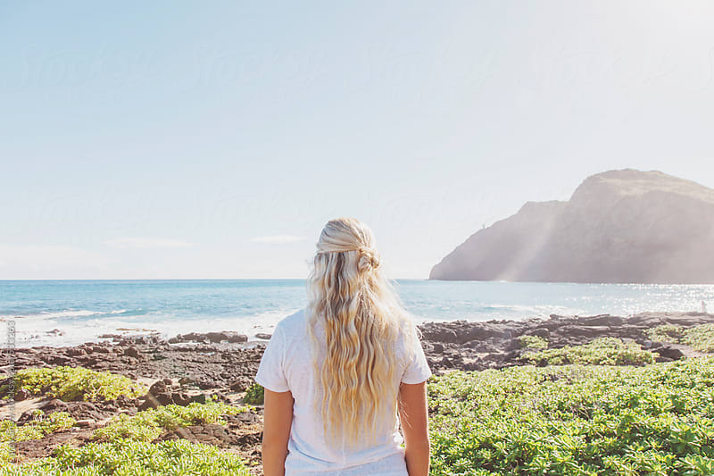Young woman looking at the ocean by Carey Shaw for Stocksy United