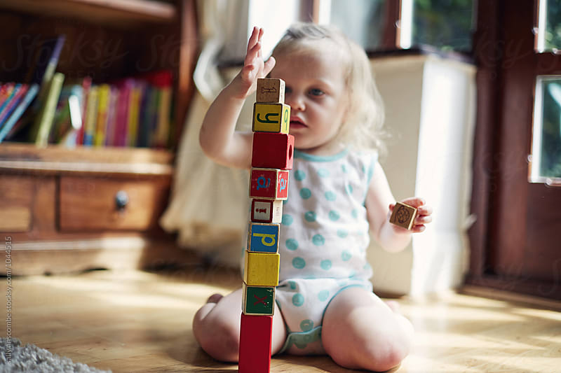 Child playing with building blocks by sally anscombe for Stocksy United