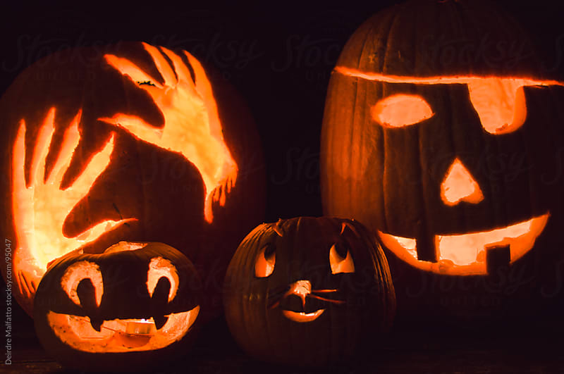 carved pumpkins (jack-o-lanterns) by candlelight on halloween by Deirdre Malfatto for Stocksy United