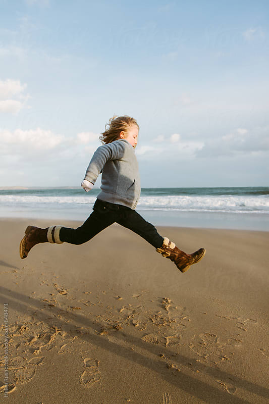 A little girl jumping on a beach by Helen Rushbrook for Stocksy United