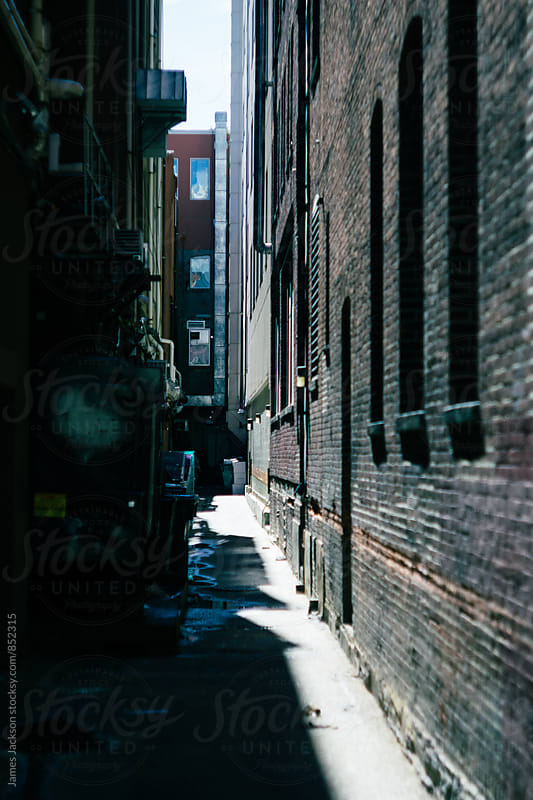 Narrow, dead end alley half lit by sunlight by James Jackson for Stocksy United