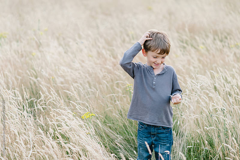 Boy exploring a meadow by Rebecca Spencer for Stocksy United