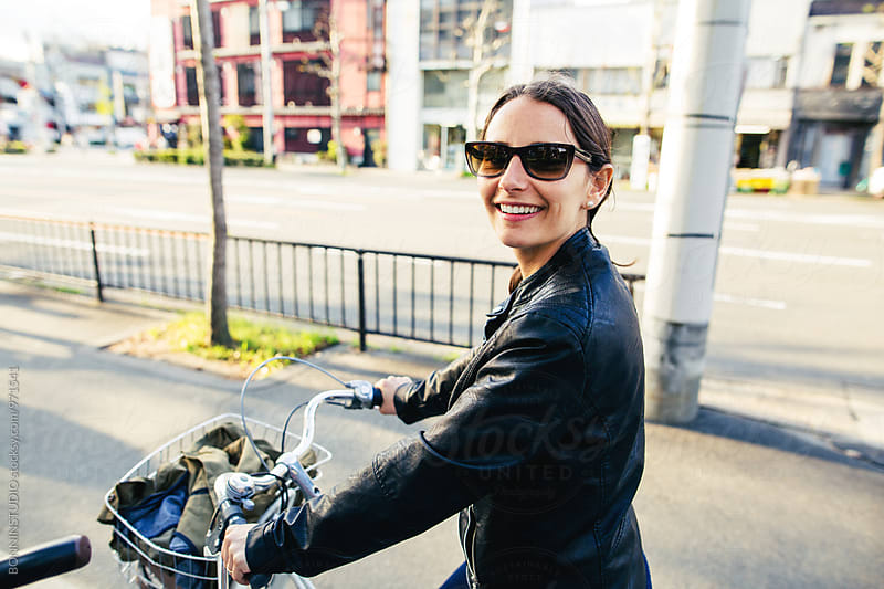 Portrait of a smiling woman riding her bicycle on the street. by BONNINSTUDIO for Stocksy United