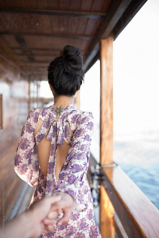 Girl holding hands with her lover walk forward on the yacht in s by Song Heming for Stocksy United