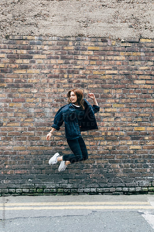 Woman jumping against a wall by HEX. for Stocksy United