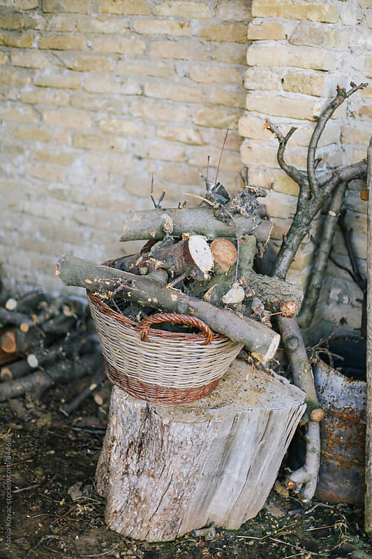 Log's in a wicker basket  by Marija Kovac for Stocksy United