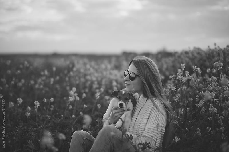 Woman enjoying nature with a Jack Russell puppy by Javier Pardina for Stocksy United