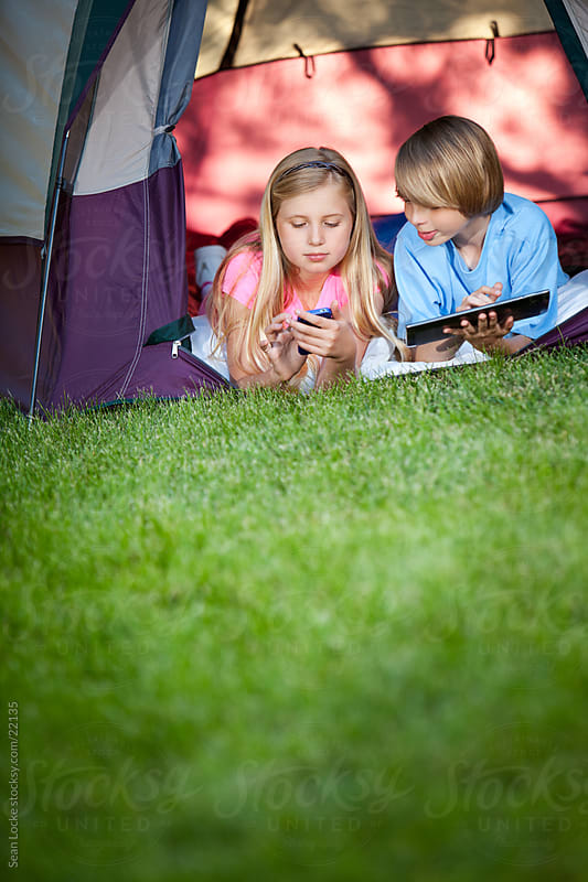 Camping: Kids Using Technology in Tent by Sean Locke for Stocksy United