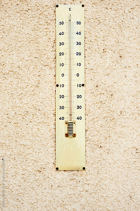 big thermometer on yellow wall by Atakan-Erkut Uzun for Stocksy United