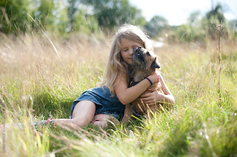 Girl hugging her dog in a sunlit field by CHRISTINA K for Stocksy United