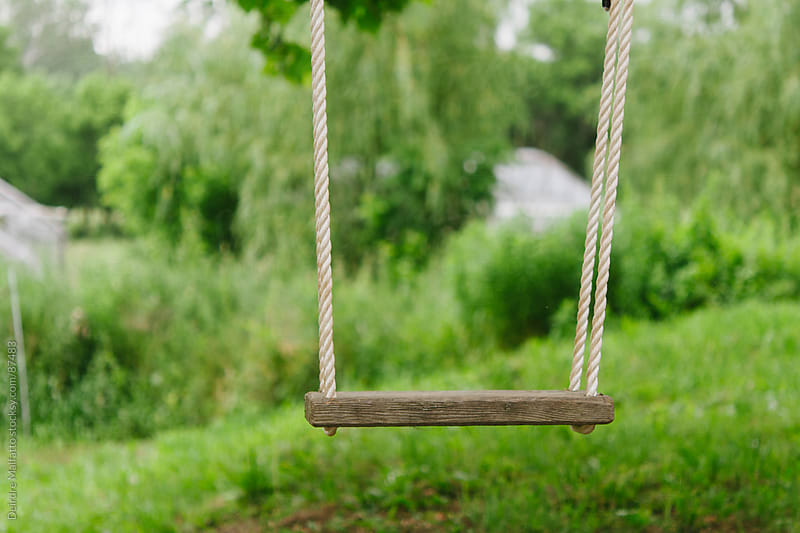 wooden swing on a farm by Deirdre Malfatto for Stocksy United