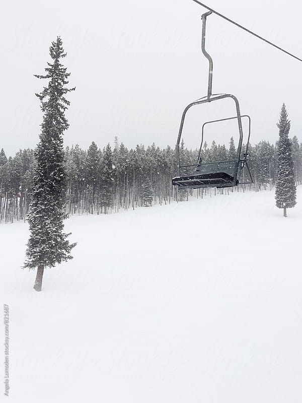A empty chairlift on a snowy day by Angela Lumsden for Stocksy United