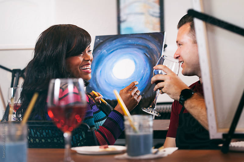 Painting: Woman And Friend Laughing During Painting Party by Sean Locke for Stocksy United
