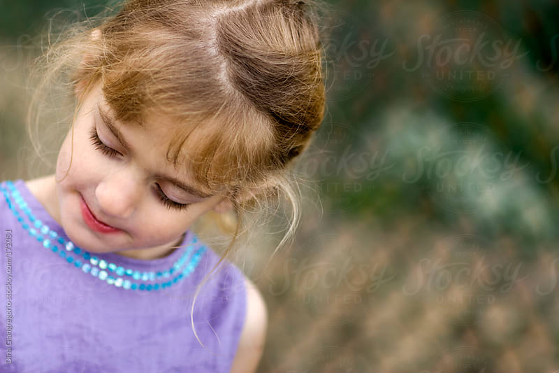 Toddler in purple dress having quiet moment by Dina Giangregorio for Stocksy United