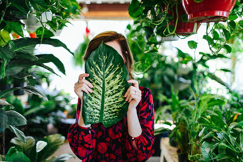 A woman holding a big plant leaf over her face by Kristen Curette Hines for Stocksy United