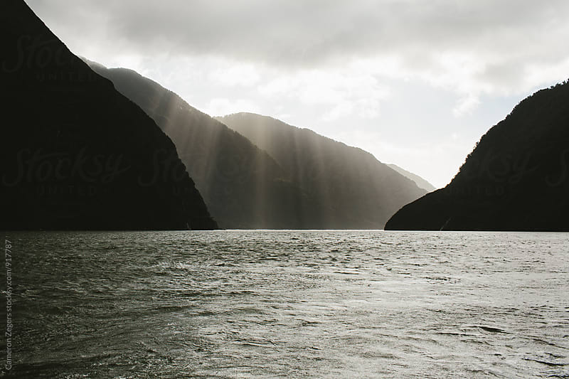 sunlight through clouds in fjord by Cameron Zegers for Stocksy United