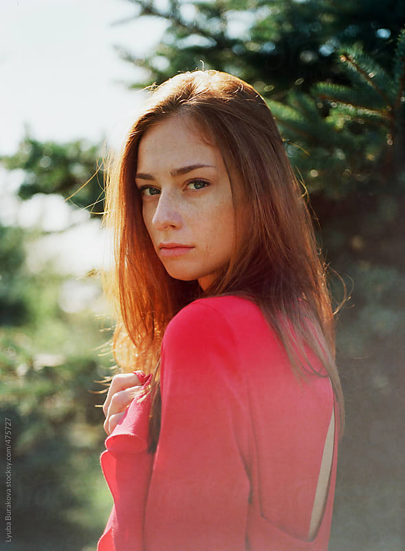 Portrait of the beautiful woman in red dress looking at camera by Lyuba Burakova for Stocksy United