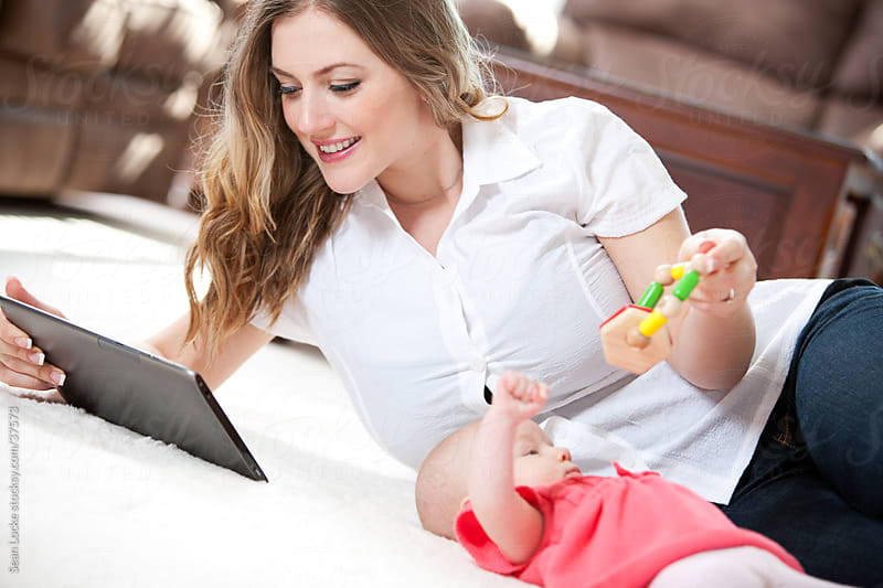 Baby: Mom Reads Digital Tablet While Playing with Baby by Sean Locke for Stocksy United