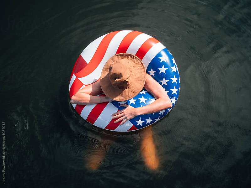 Girl wearing hat in American Flag float in lake by Jeremy Pawlowski for Stocksy United