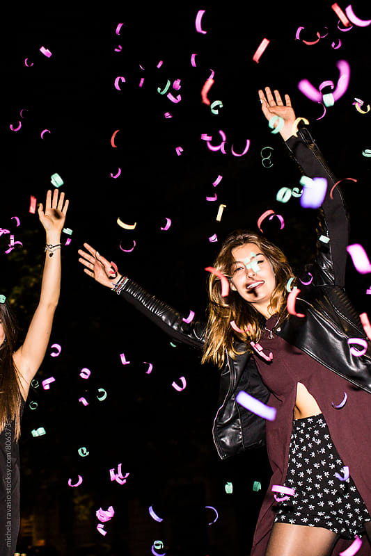 Happy young woman celebrating on the streets with confetti by michela ravasio for Stocksy United