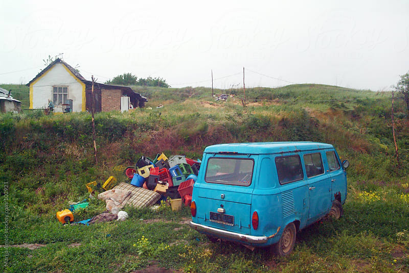 blue van and trash in front of the little ,poor gypsies home by Marija Anicic for Stocksy United