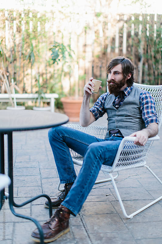 Trendy and stylish bearded man at a coffee shop by Jakob for Stocksy United