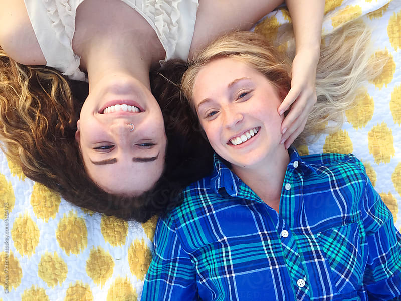 Friends laying on a blanket laughing by Chelsea Victoria for Stocksy United