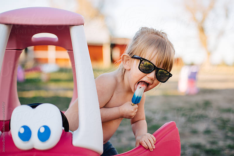 Small child eating popsicle with sunglasses on by Jessica Byrum for Stocksy United