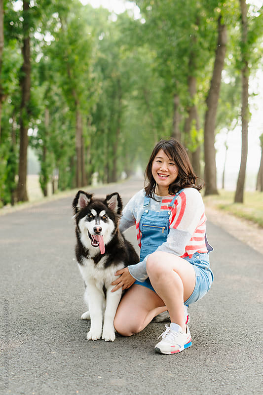 Pregnant young woman with her Alaskan malamute by Maa Hoo for Stocksy United