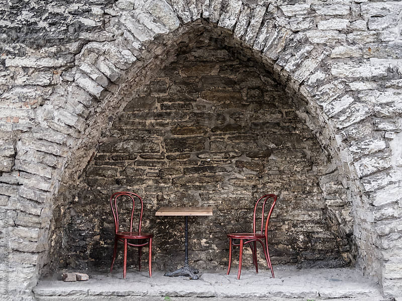 Empty chairs and table of an outdoor cafe in the niche of an old wall by Melanie Kintz for Stocksy United