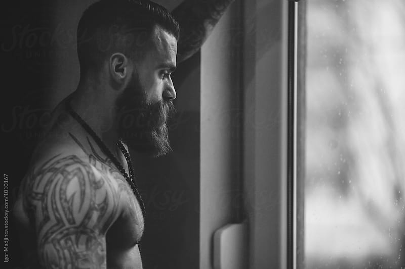 handsome and sexy tattooed hipster mature man with a cross by Igor Madjinca for Stocksy United