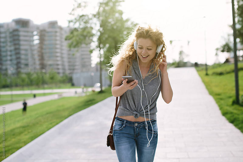 Young blond woman listening to music outdoors by Davide Illini for Stocksy United