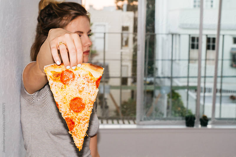 young female holding slice of pizza in front of face by Jesse Morrow for Stocksy United