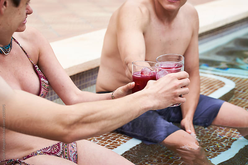 Unrecognizable friends  toasting with drinks in pool by Guille Faingold for Stocksy United
