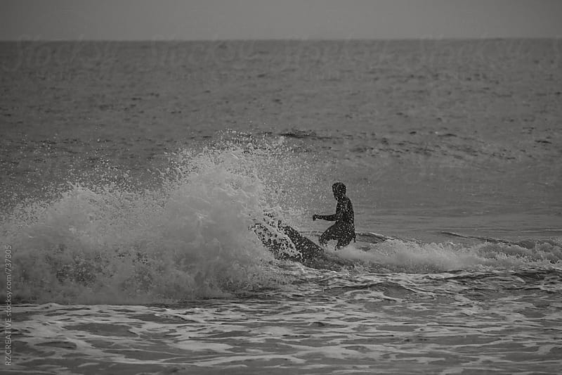 Black and white image of a surfer riding a wave. by Robert Zaleski for Stocksy United