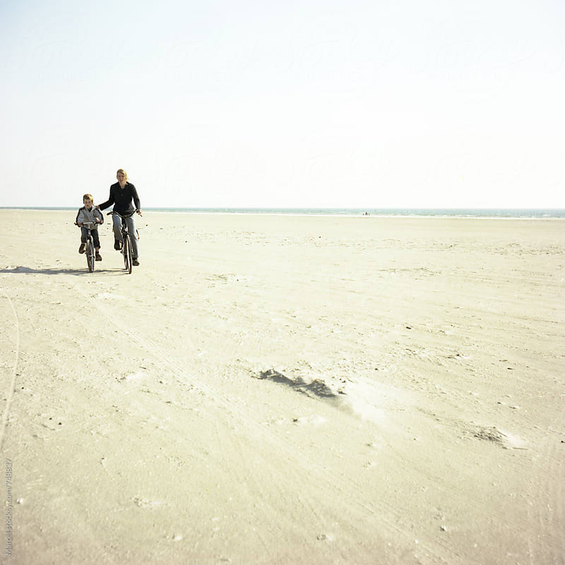 Mother and son cycling on the beach by Marcel for Stocksy United