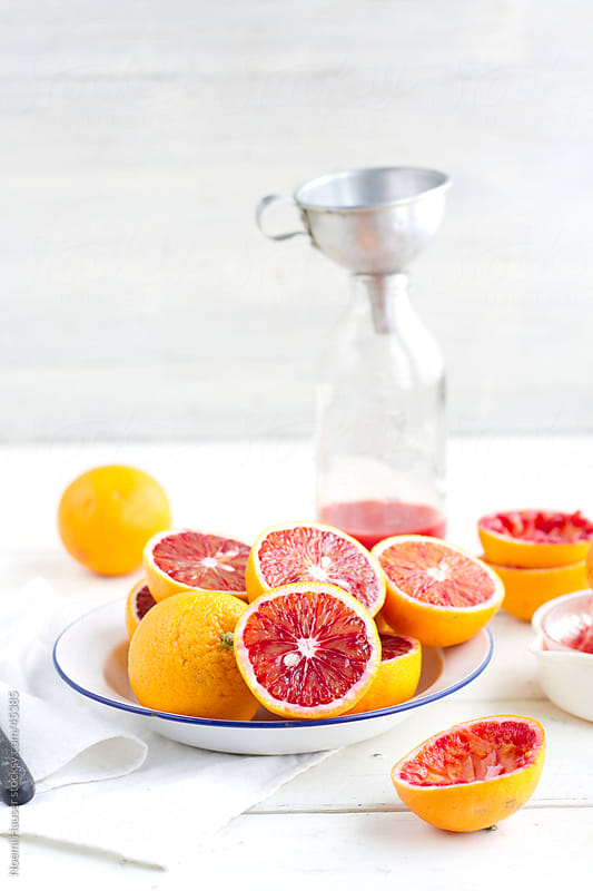 Blood oranges halved and whole on plate by Noemi Hauser for Stocksy United
