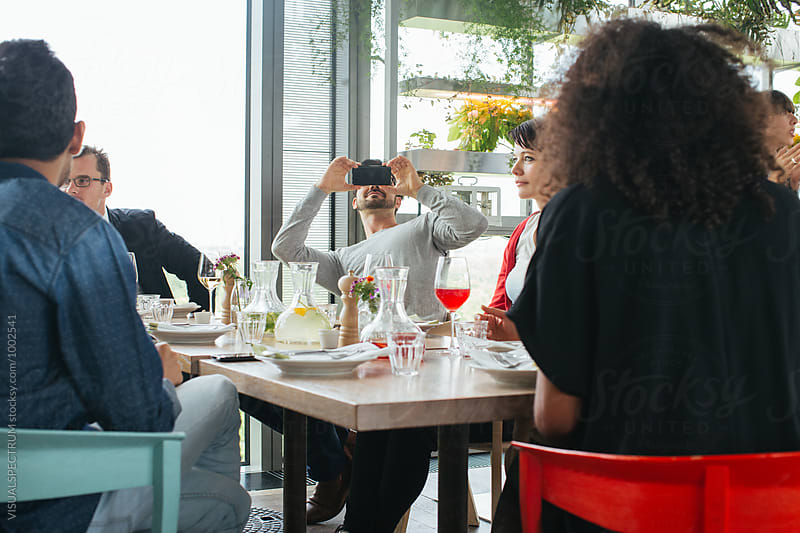 Lunch With Friends - Caucasian Man Taking Smartphone Photo of Friends in Bright Restaurant by VISUALSPECTRUM for Stocksy United