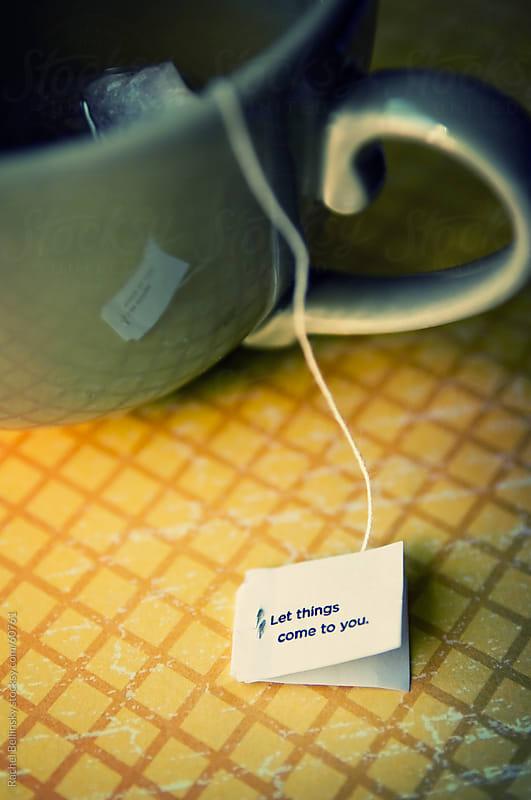 Green mug with hot tea with teabag words of wisdom by Rachel Bellinsky for Stocksy United