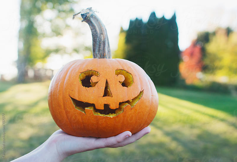 Small carved jack o'lantern held by hand by Tana Teel for Stocksy United