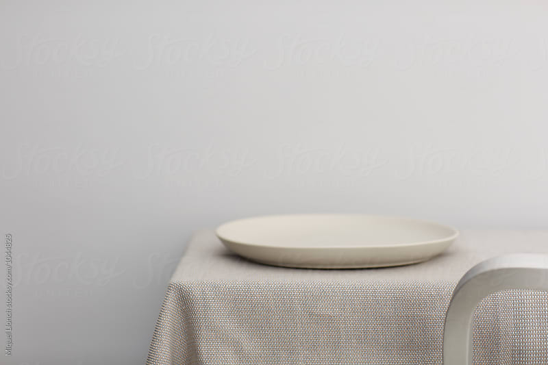 Table and plate and detail of a chair by Miquel Llonch for Stocksy United