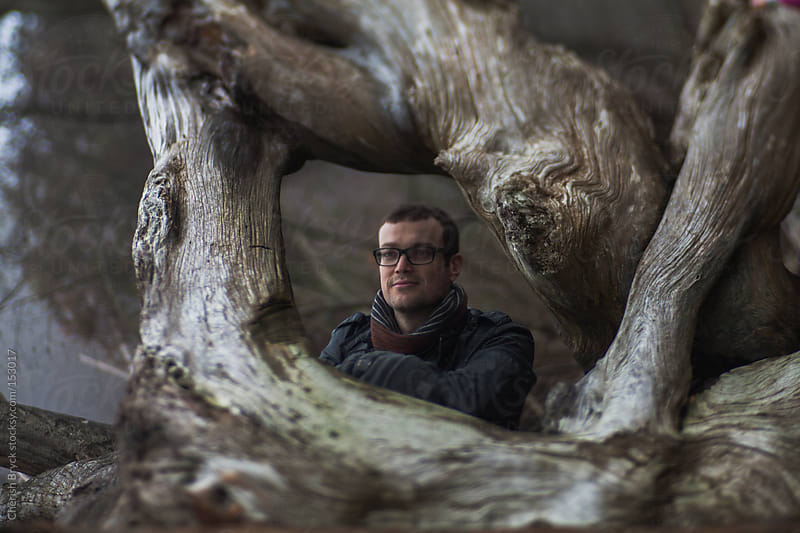 Man framed by fallen tree branches. by Cherish Bryck for Stocksy United