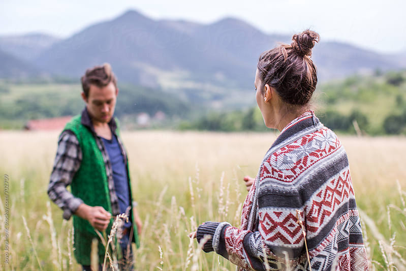 Man and woman standing in a field of wild grass by Jovo Jovanovic for Stocksy United