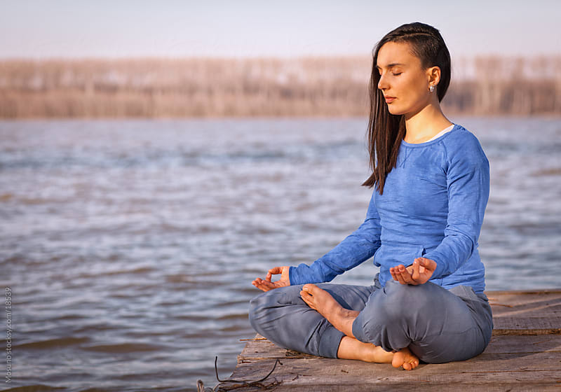 Young woman meditating by the river. by Mosuno for Stocksy United